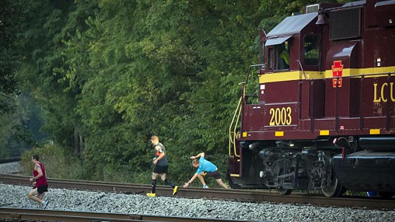 Marathonlopers springen weg voor passerende trein
